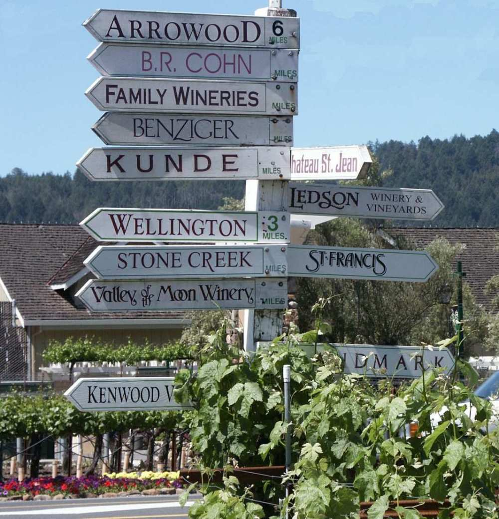 Road sign displays multiple directions for vineyards and wineries in Sonoma Valley which are near The Big and Juicy Grape.