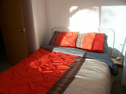The Orange Room's metal frame queen size bed, side table, lamp, bedspread, natural light coming through window.