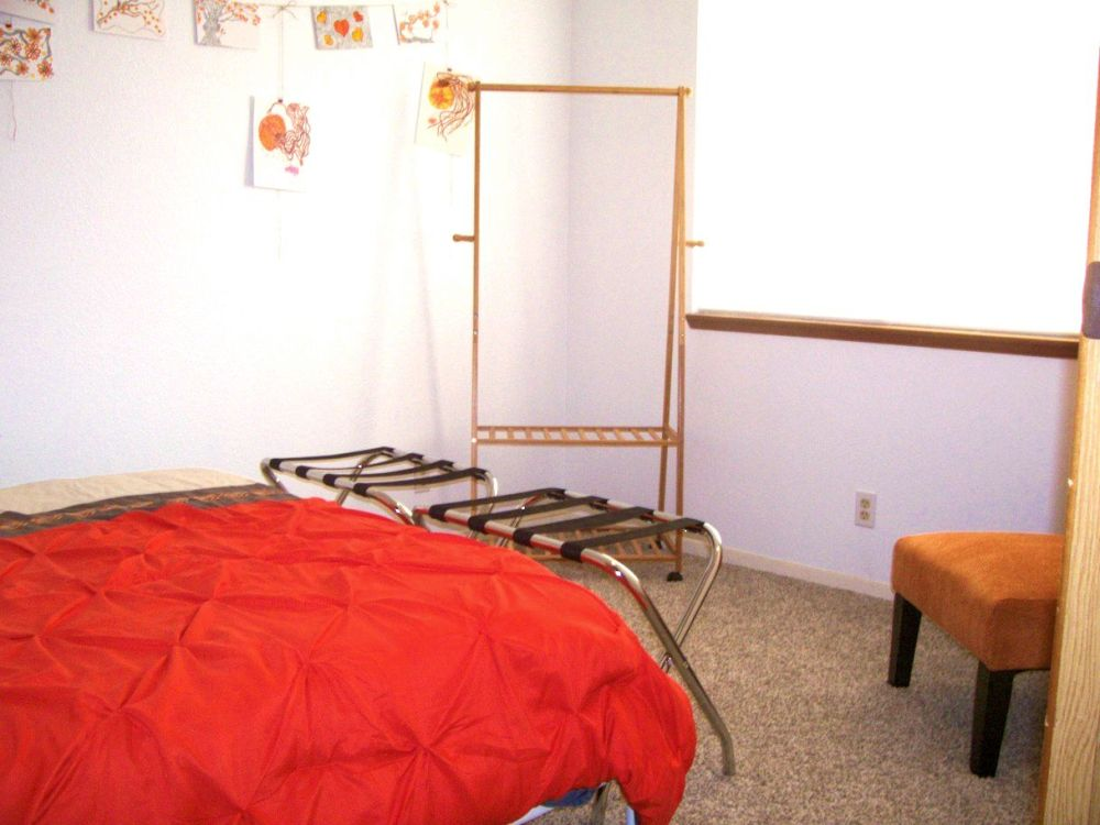 Open clothes hanging rack, luggage racks, queen bed and artwork.
